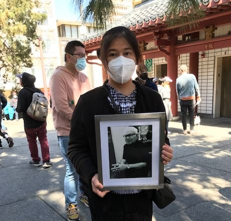 Mounthanus Ratanapakee holds a photo of her father Vicha Ratanapakdee.
